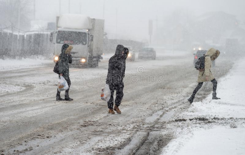 A snowstorm in the city. People cross the snowy road in front of cars stock photography