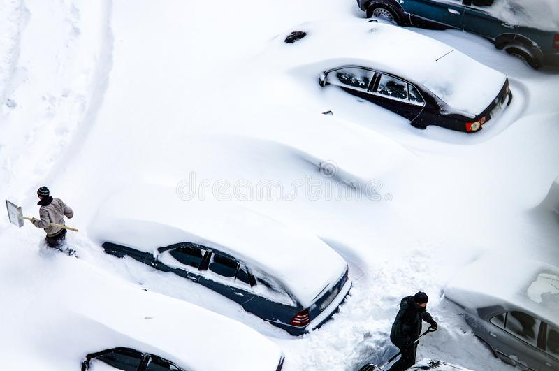 After a snowstorm, people dig out cars from under snow royalty free stock images