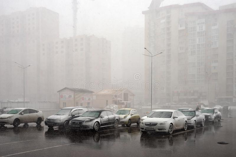 Snowstorm suddenly from crashing on cars parked on the square in a residential area of the city of Krasnoyarsk. royalty free stock image