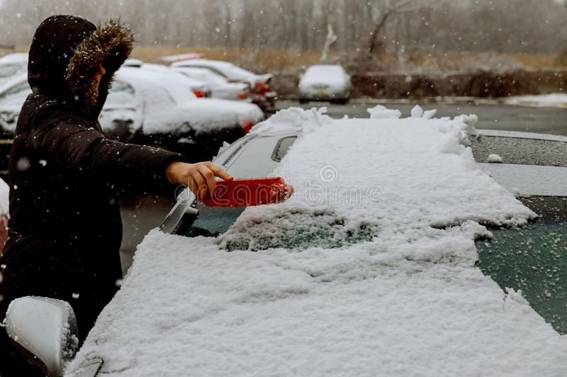 woman shoveling and removing snow from her car, stuck snow royalty free stock photography