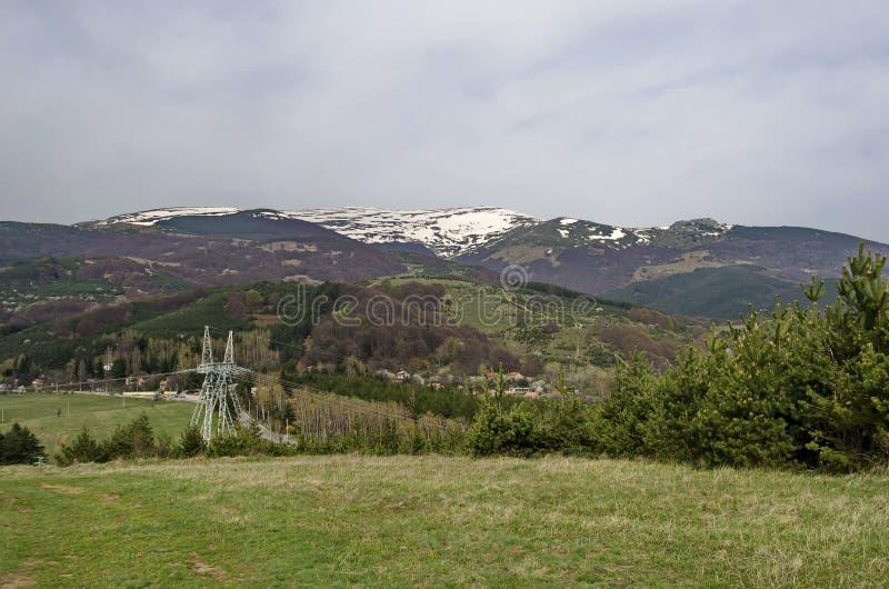 Snowy übersteigen, Frühjahrfuß des Berges, Lichtung, Mischungswald, elektrische Hochspannungsleitung und Wohnviertel stockbild