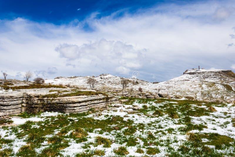 Snowy и пасмурный ландшафт весной с изображением утеса и травы горы на переднем плане - стоковые изображения