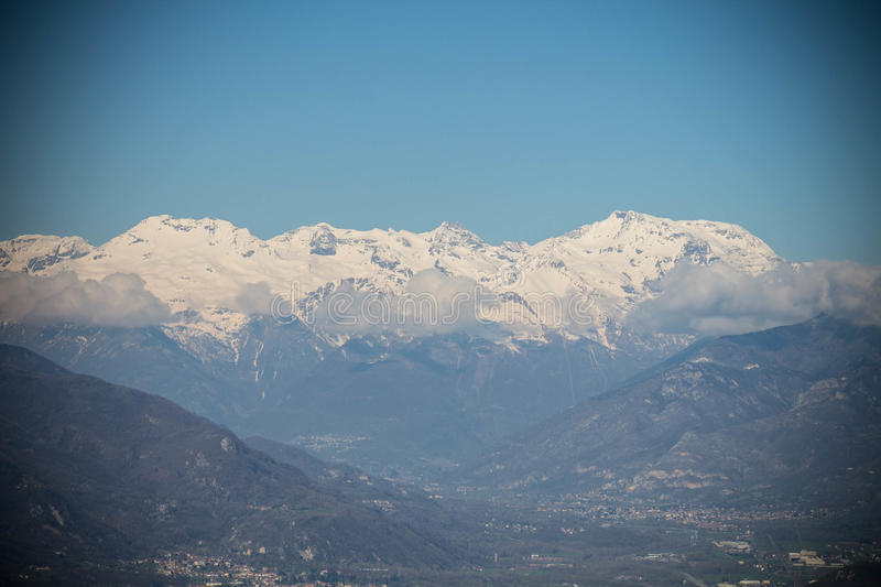 Snowy Alps and clouds in Val di Susa. Vignette effect. Piedmont. Italy royalty free stock photos