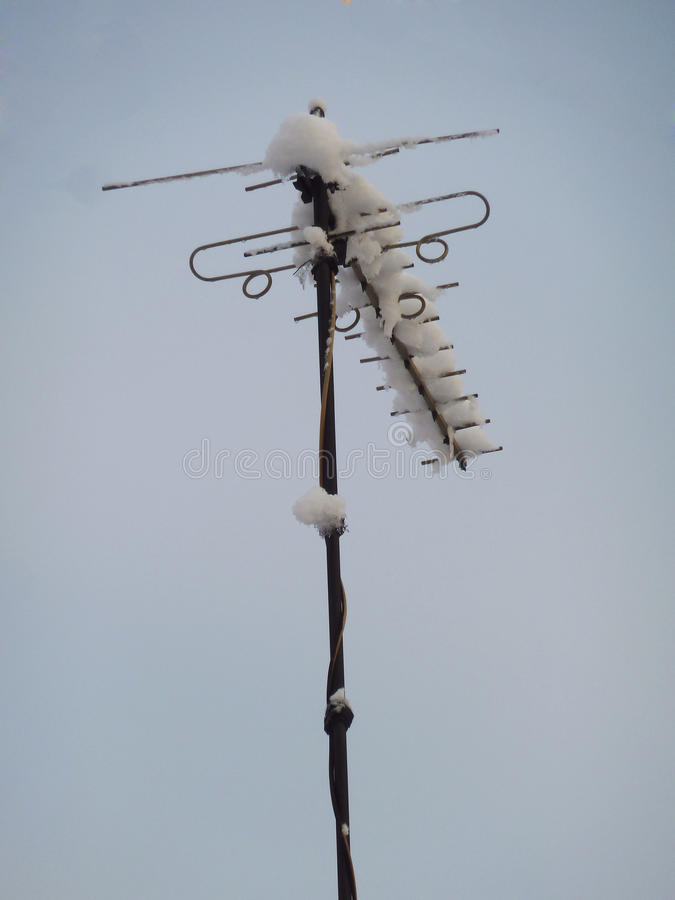 Snowy antenna on the roof royalty free stock image