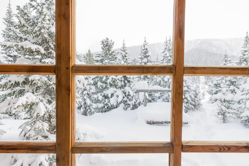 Snowy-Bäume des Waldes im Schnee außerhalb des Fensters mit einem hölzernen lizenzfreies stockbild