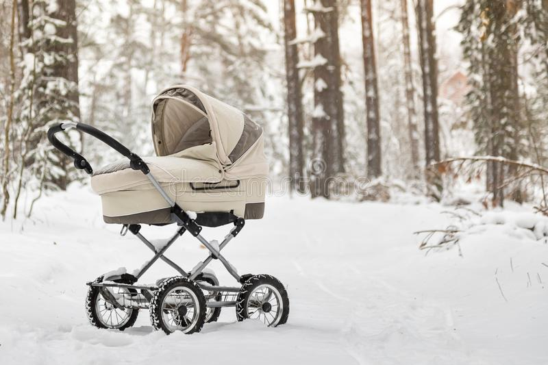 Snowy baby stroller in winter forest. tire tracks on snow. Infant baby sleep inside the pram on fresh air.  stock image