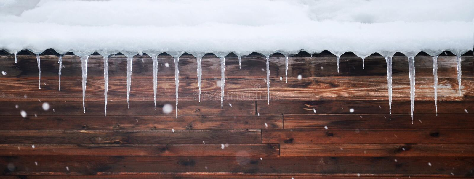 Snowy background with icicles and snowflackes stock photography