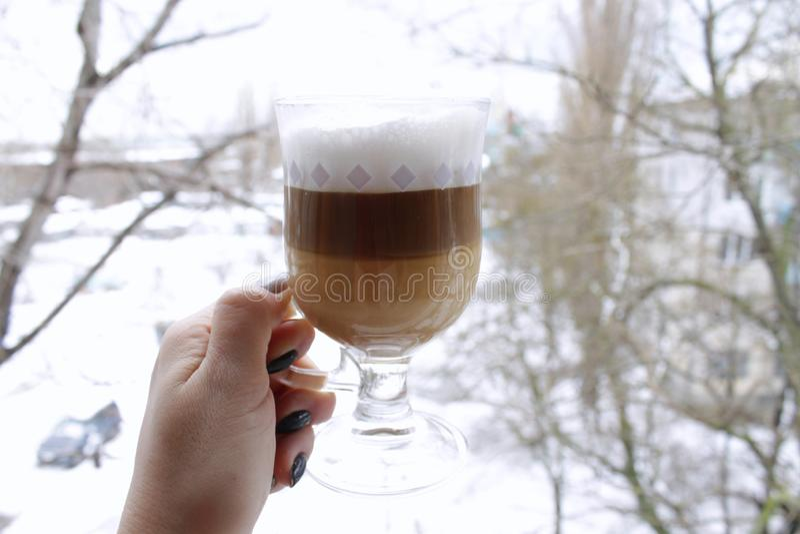 On snowy background, transparent mug of aromatic cappuccino, amnricano, latte royalty free stock photo