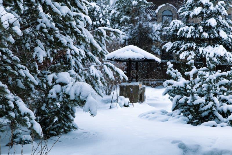 Snowy Backyard Patio Winterlandschap met barbeque, sneeuwbanken van witte sneeuw, pijnbomen in de tuin van het land royalty-vrije stock afbeeldingen