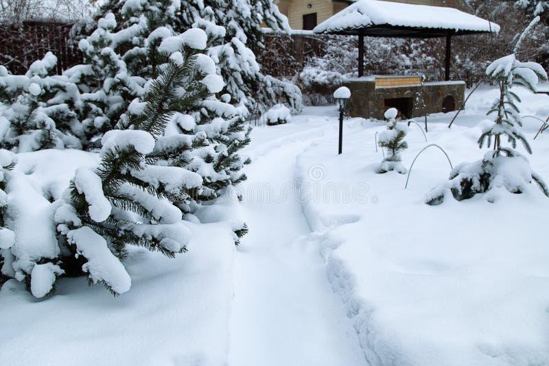 Snowy Backyard Patio Winterlandschap met barbeque, sneeuwbanken van witte sneeuw, pijnbomen in de tuin van het land royalty-vrije stock fotografie