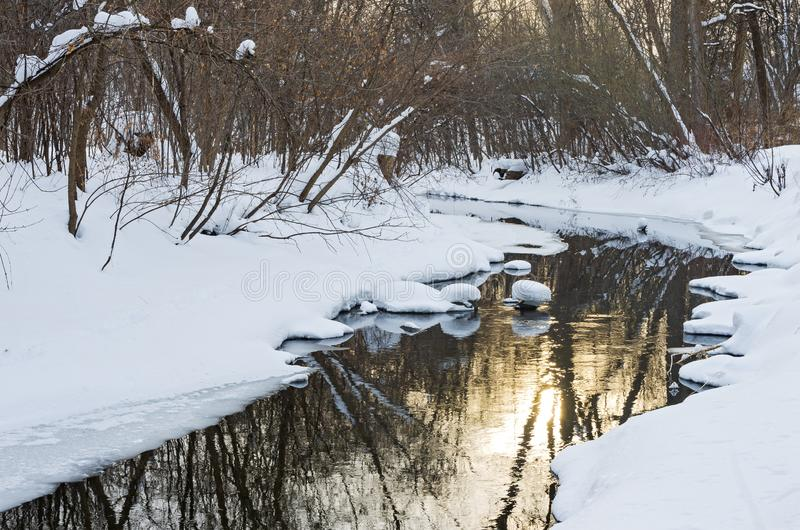 Snowy Banks and Reflections off Waters of Minnehaha Creek. Snowy banks of minnehaha creek flowing through woodlands of minnehaha parkway and sun reflecting off stock image