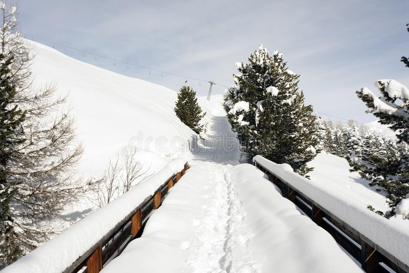 A snowy bridge in the snow covered landscape and mountains in the alps switzerland in winter stock photography