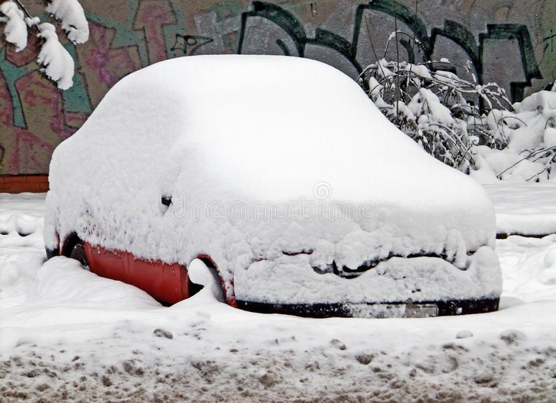 Snowy car in calamity. Red snowy car parked in pile of snow stock image