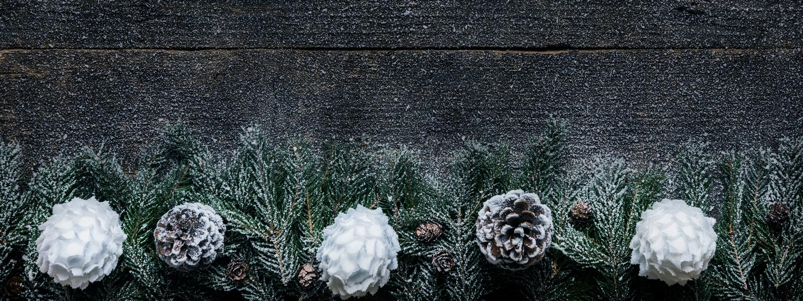 Snowy Christmas Background, Fir Tree Branches With Pine Cones And Xmas Baubles On Wooden Background stock photos