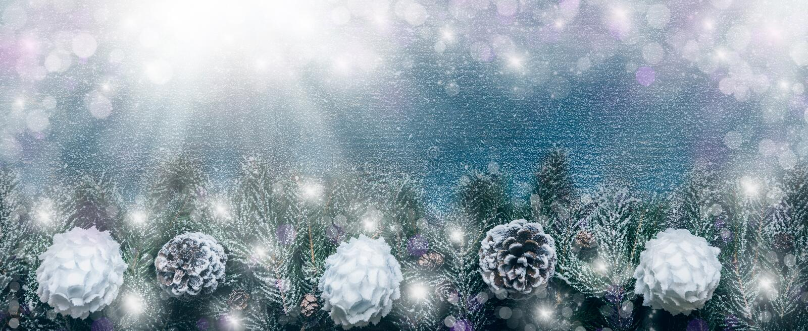 Snowy Christmas Background, Fir Tree Branches With Pine Cones And Xmas Baubles On Wooden Background royalty free stock image
