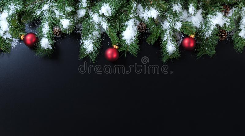 Snowy Christmas branches with red ornaments on black background royalty free stock photos