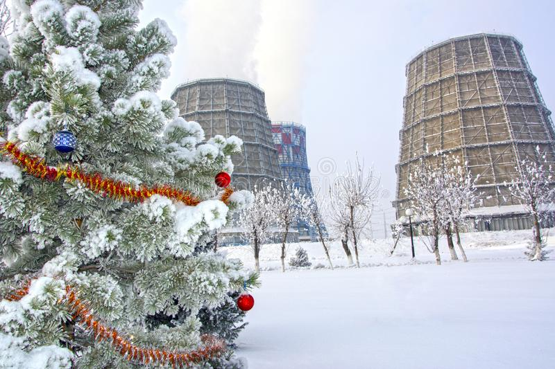 Snowy Christmas tree decorated with toys. Against the background of industrial objects stock image