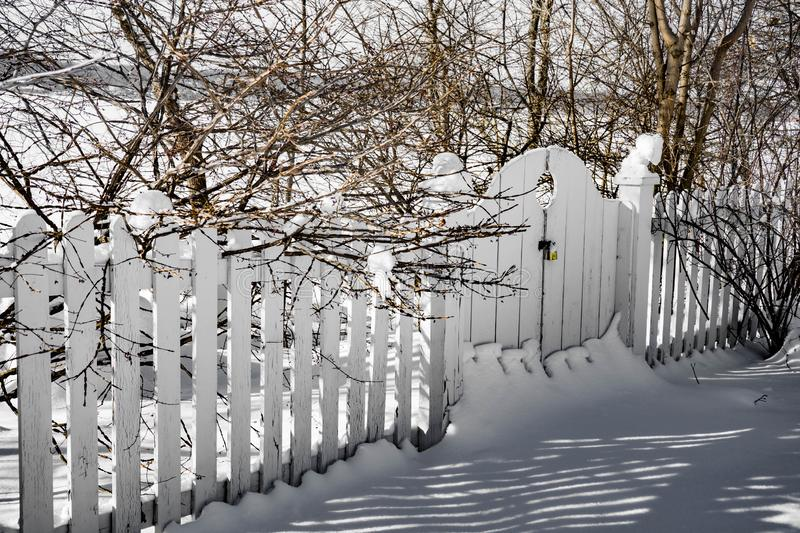 Snowy-covered white fence and gate at winter garden stock photo