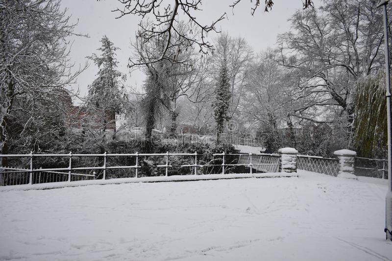 Snowy day in Leamington Spa UK, view of the small bridge over Leam River, Pump Room Gardens - 10 december 2017. Image with the small bridge from Pump Room stock photography