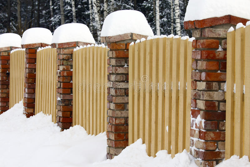 Snowy fence. Brick and wood fence covered with snow royalty free stock photo