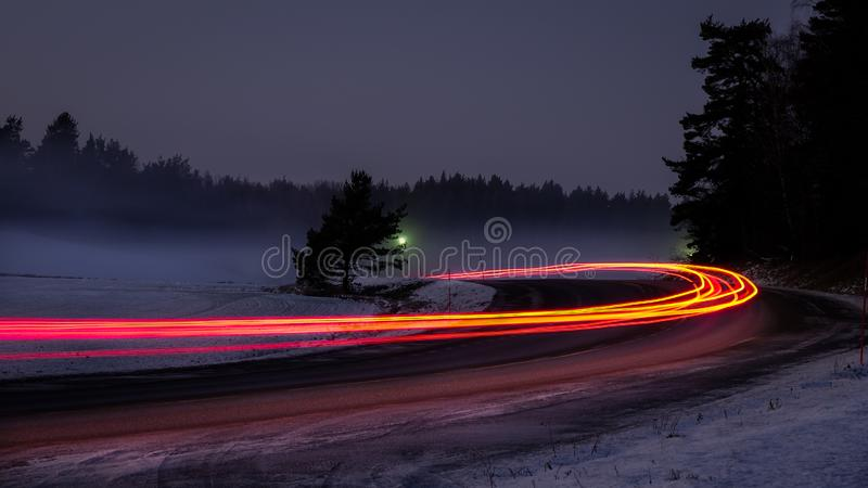 Snowy foggy forest road with car tail lights. royalty free stock photography