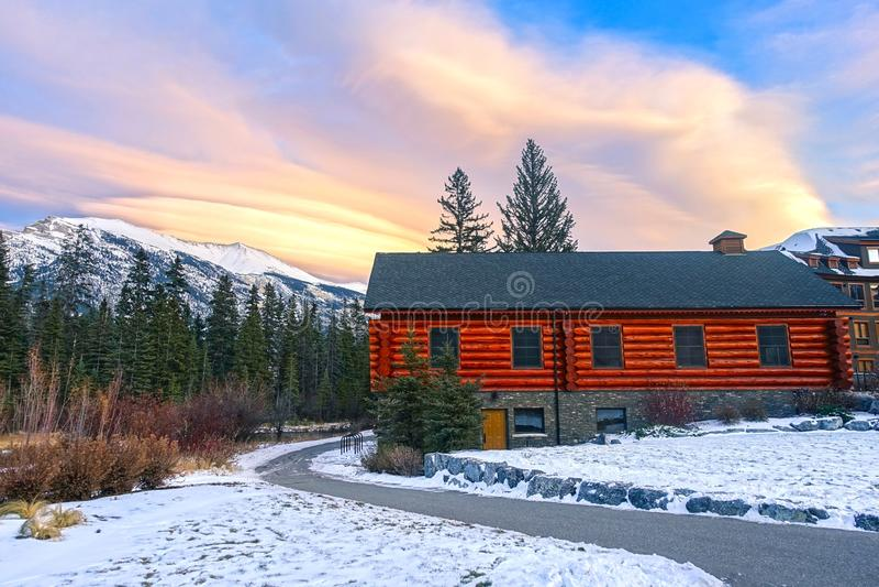 Snowy Footpath Rustic Wooden Alpine Log Cabin Snowy Mountain Peak Sunset Sky Colors Canmore Alberta royalty-vrije stock afbeeldingen