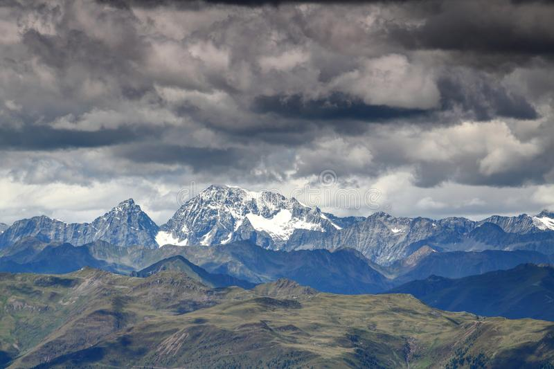 Snowy Hochgall / Collalto peak under dark clouds, High Tauern. Snowy Hochgall / Monte Collalto and Wildgall / Collaspro peaks, ridges of Rieserferner and royalty free stock photo