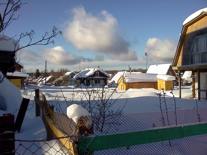 Snowy houses in suburban village. Late sunny winter days. stock photo