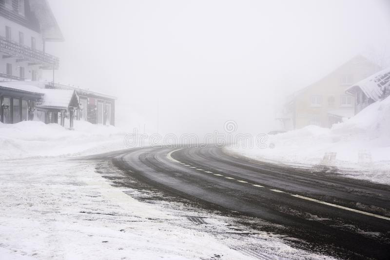 Snowy and icy road curve in a foggy weather - Vosges mountains stock image