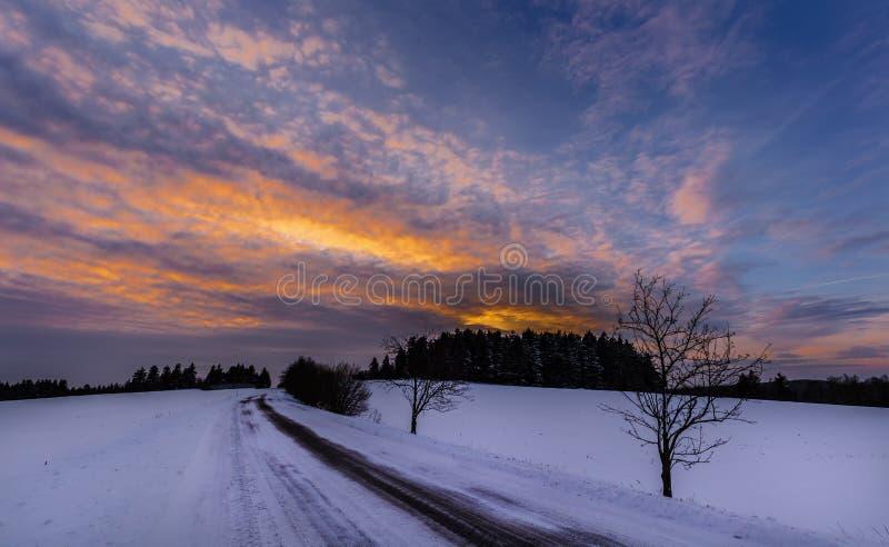 Snowy-Landschaft und -straße bei Sonnenuntergang stockfotografie
