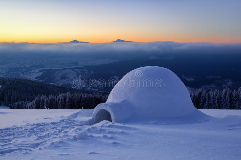 On the snowy lawn in the snowdrift there is an igloo. On the snowy lawn in the snowdrift there is an igloo covered by snow with the background of mountains stock photo
