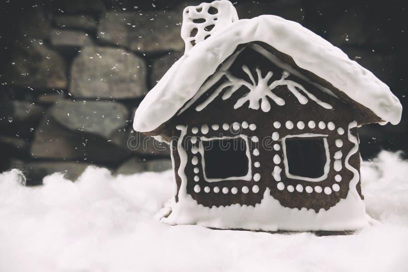 Snowy-Lebkuchenhaus mit SchneeflockenWeihnachtsbaum und Kugel auf Steinwandhintergrund Selbst gemachte Weihnachtsplätzchen - ging stockfotos
