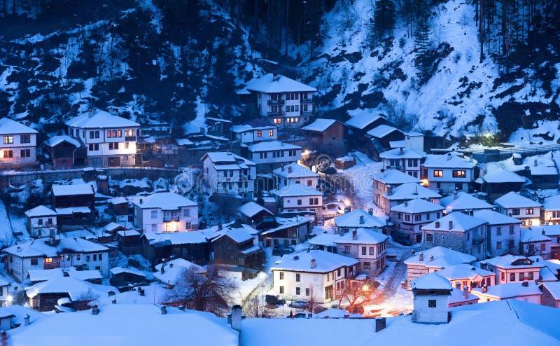 Snowy-Märchen in Bulgarien Nacht geht unten über Dorf Shiroka Laka, Bulgarien hinaus stockfotografie