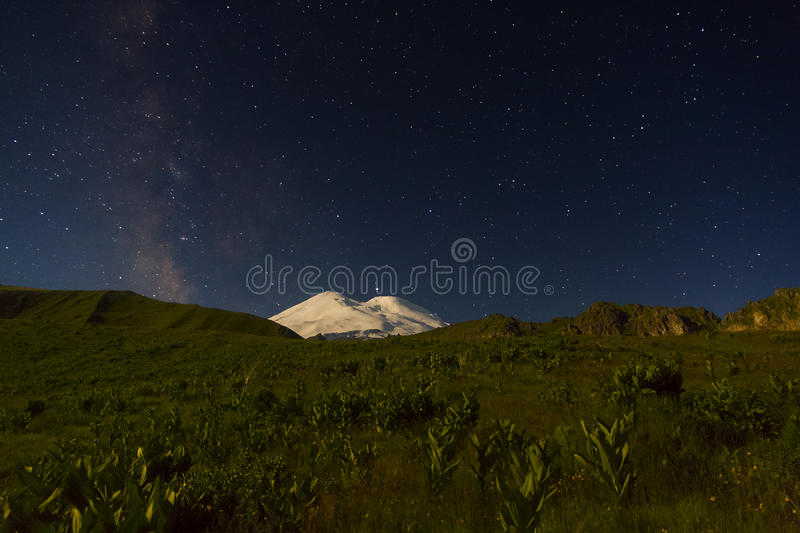 Snowy mountain Elbrus in moonlight, Milky Way stars and Saturn at night. Snowy mountain Elbrus (5642 m) in moonlight, Milky Way stars and Saturn at night royalty free stock photo