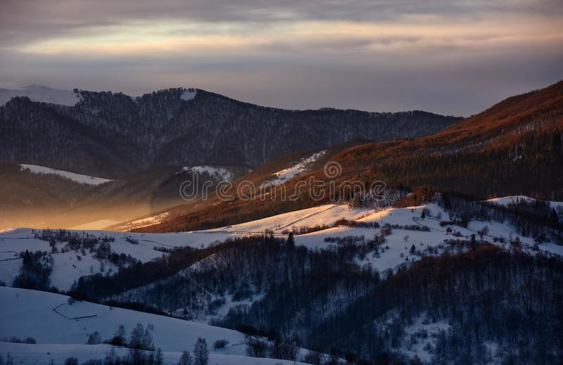 Snowy mountain hills at sunrise stock images