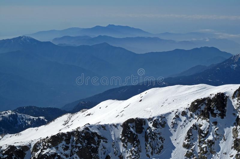 Snowy mountain lansdscape with mountain layers, ocean view in the background, Corsica, France. Europe royalty free stock image