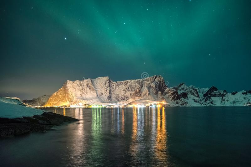 Snowy mountain range with aurora borealis and shining city stock photography