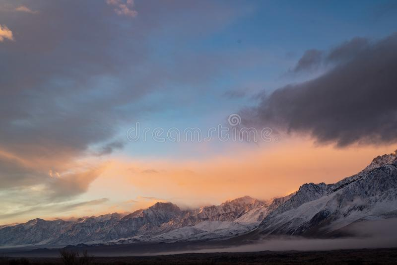 Snowy mountain range pink dawn clouds stock images