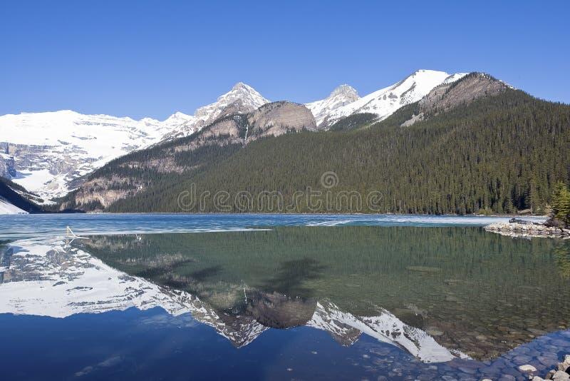Snowy mountain reflection on lake Louise - Banff , Alberta, Canada. Snowy mountain reflection on half frozen lake Louise - Banff , Alberta, Canada. Shot was stock photos