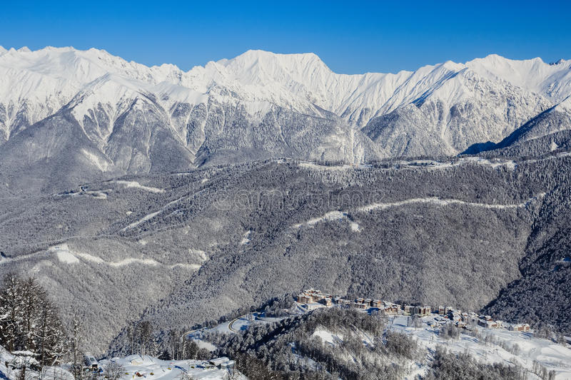 Snowy mountain ridge and group of the hotels in Rosa Khutor ski resort Sochi. Snowy mountain Caucasian ridge covered with evergeen forest and group of the hotels stock image