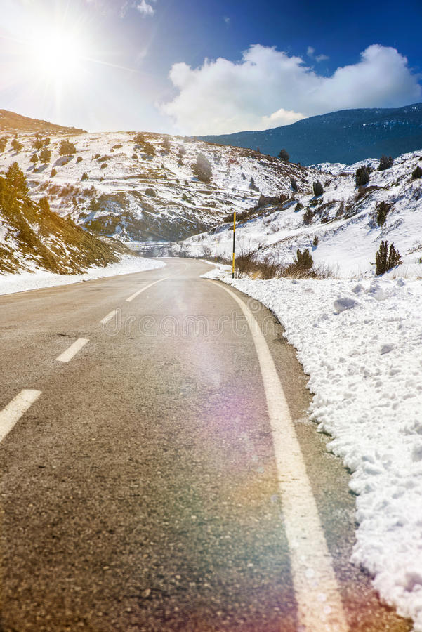 Snowy mountain road and sun stock image
