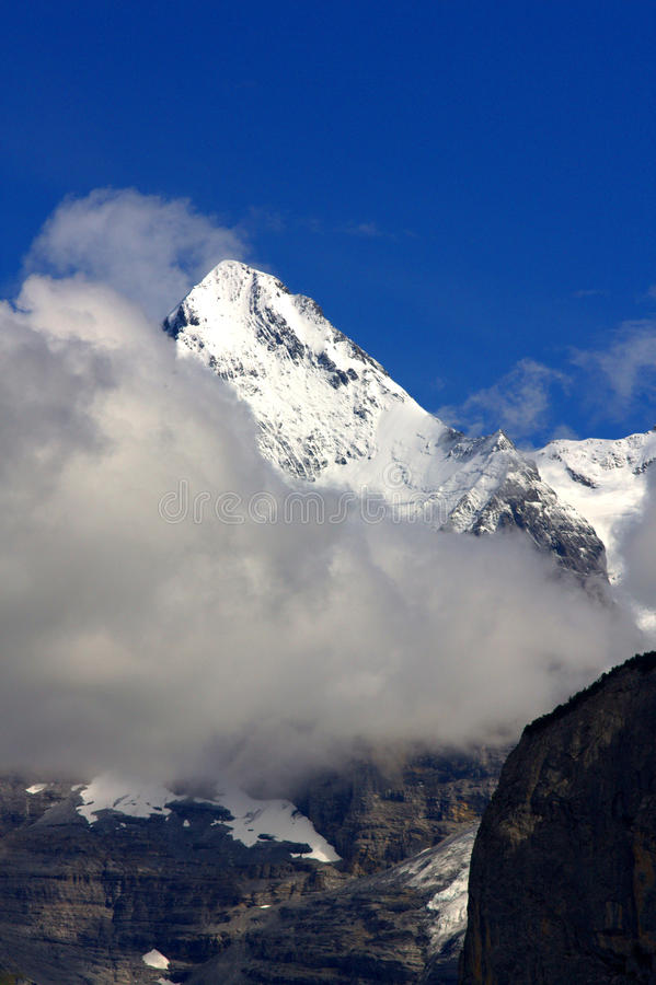 Free Snowy Mountain Top With Clouds And Sunny Blue Sky Royalty Free Stock Photos - 16064408