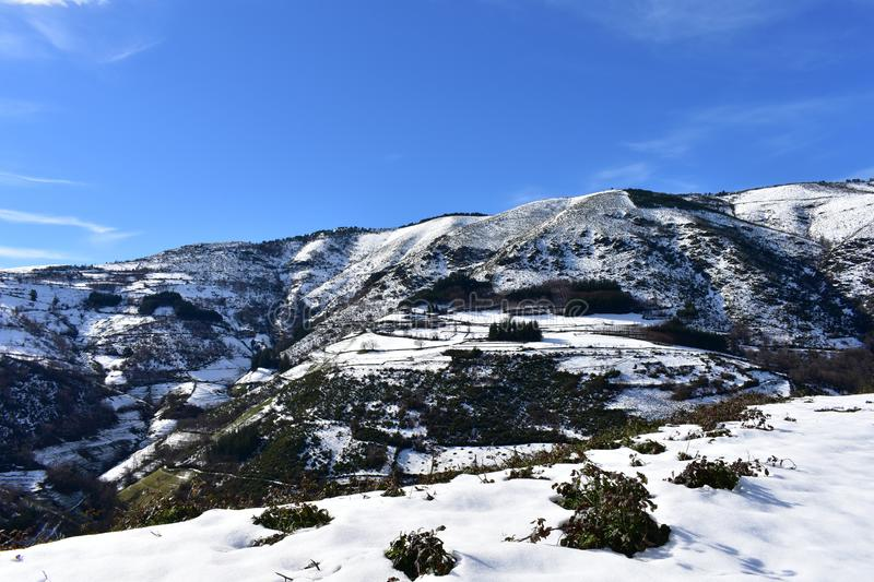 Snowy mountain with trees and small village on a slope. Ancares Region, Lugo Province, Galicia, Spain. Ancares Region, Lugo Province, Galicia, Spain. Winter stock image