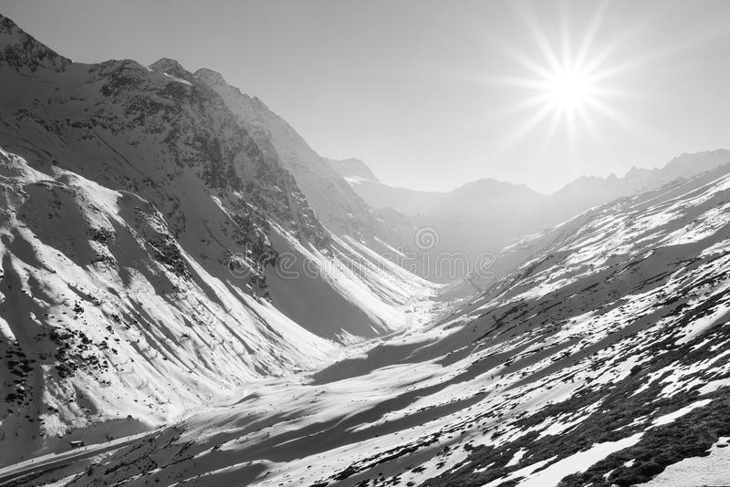 Snowy mountain valley in the sun. Black-and-white photograph. Mountain peaks on the horizon and the sun with rays royalty free stock images