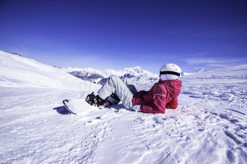 Snowy mountain view. Young woman snowboarder relaxing on the top of the mountain and watching the view stock image