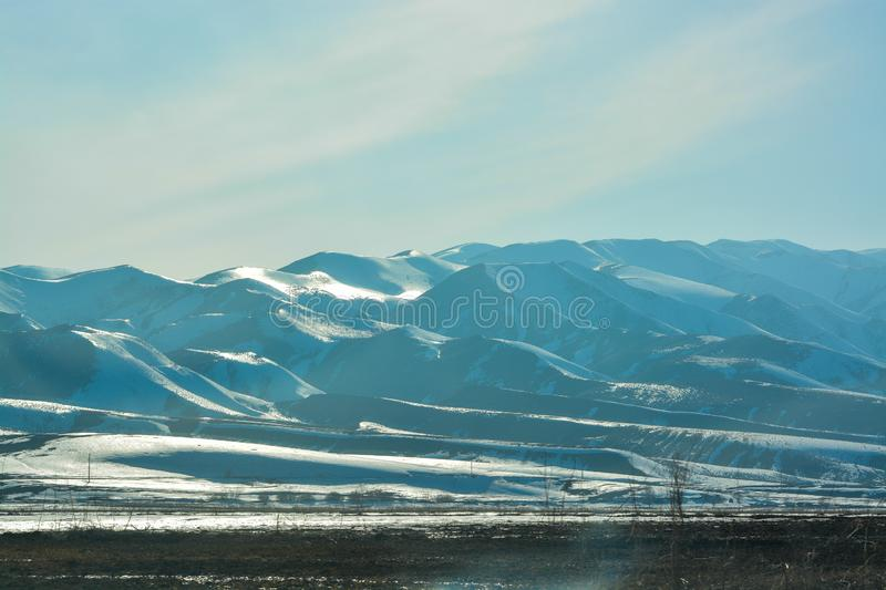 Snowy mountains `Alatau`. Lighting at noon. Spring season. At the foot of the mountain `Tien Shan.` royalty free stock photo