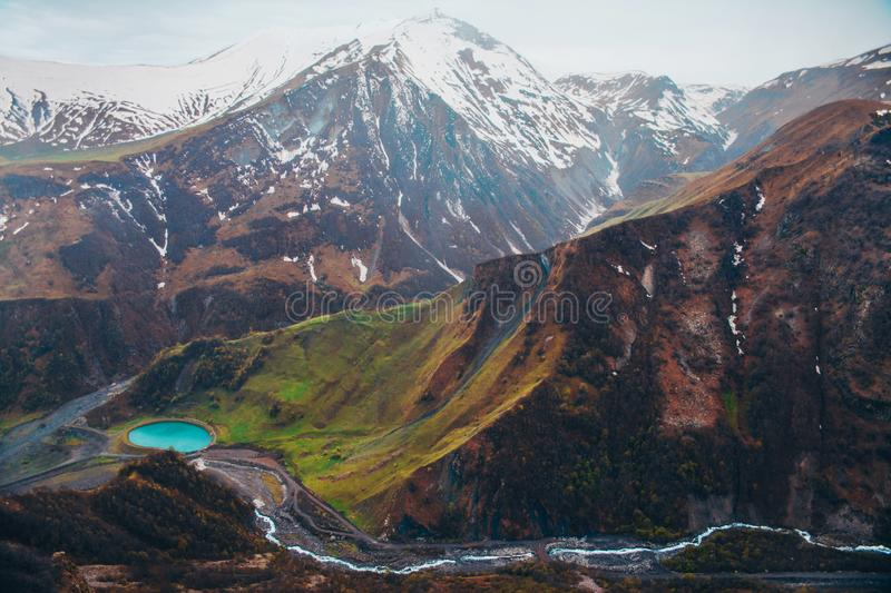 Snowy mountains and blue lake in green valley royalty free stock photography