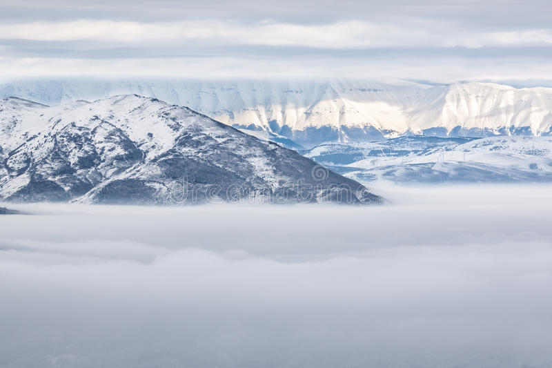 Snowy mountains with fog royalty free stock photography