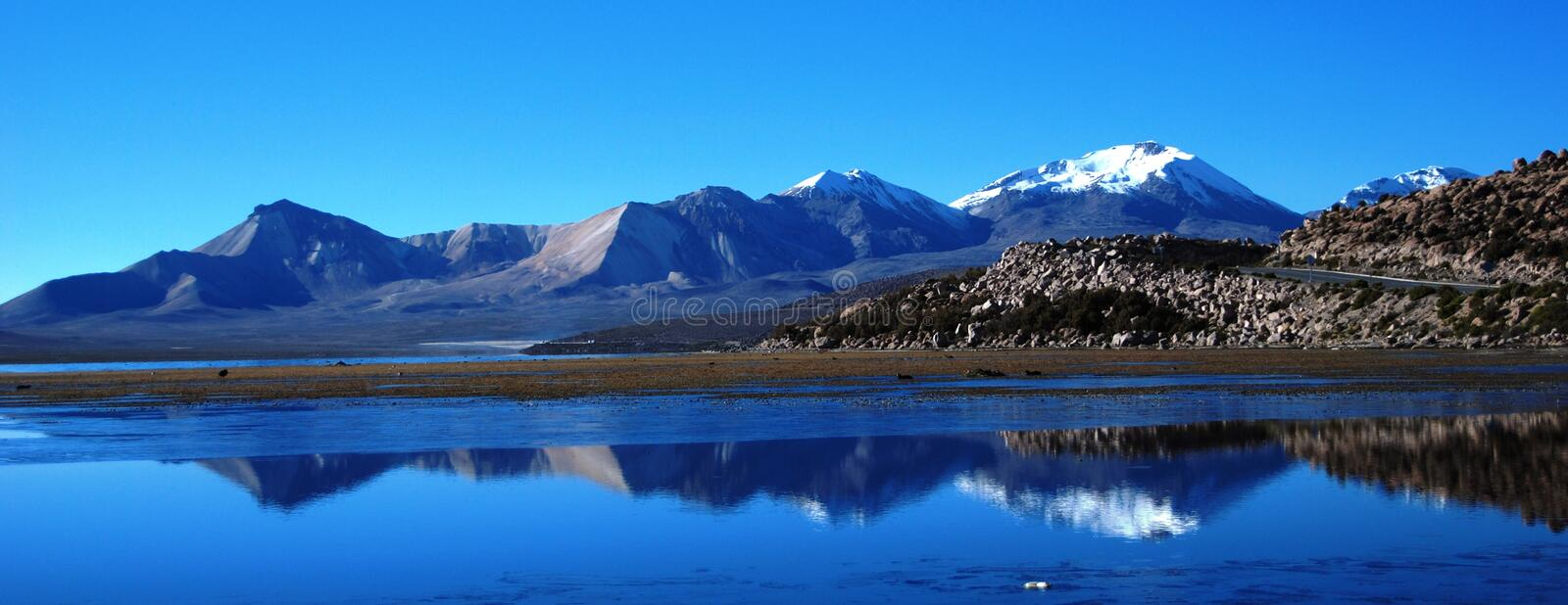 Snowy mountains reflection above lake stock image