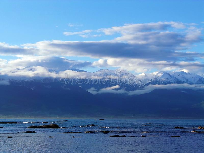 Snowy Mountains Meet the Sea royalty free stock images